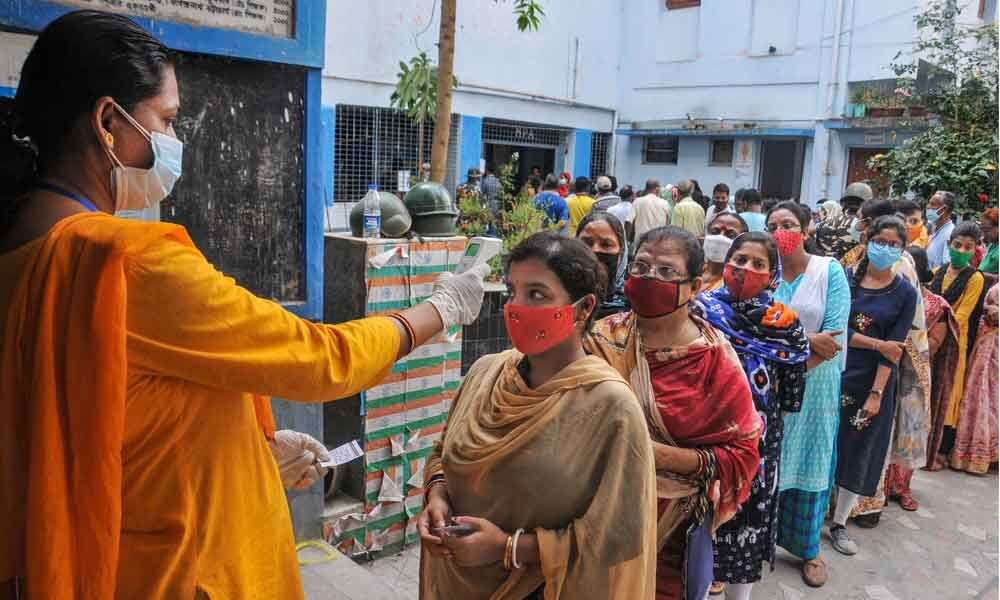 Voters undergo thermal screening as they stand in a queue to cast their votes at a polling station during the third phase of West Bengal Assembly elections. (L) BJP leader E Sreedharan and his wife Radha Sreedharan
